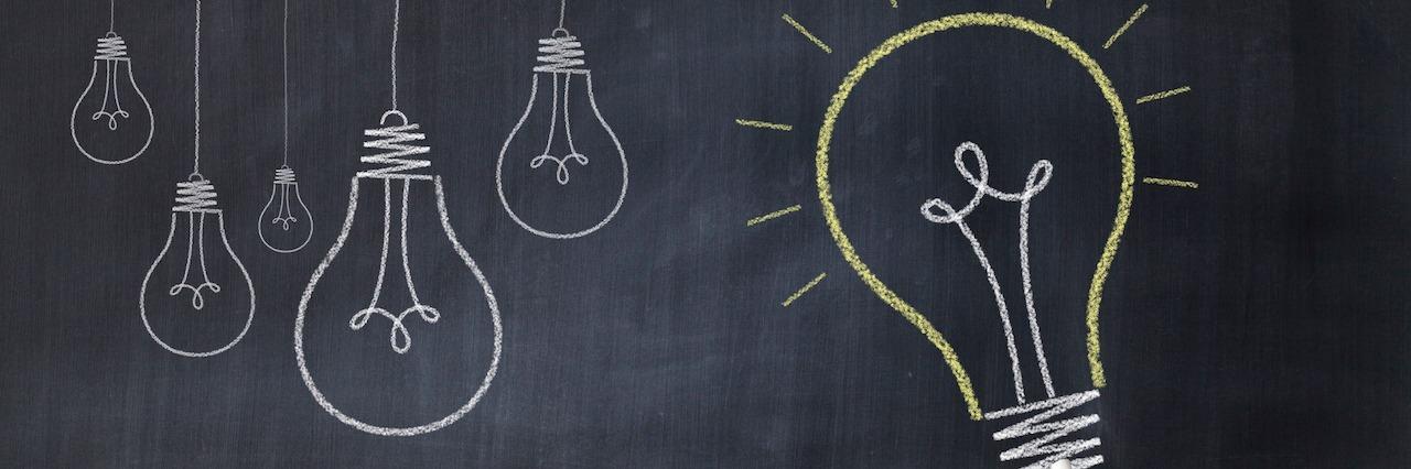 Hand drawing big light bulb on blackboard