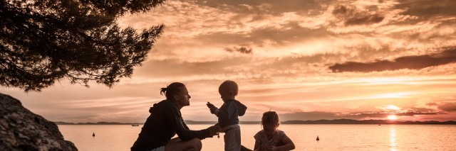 silhouette of mother playing with children on a beach at sunset
