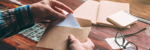 a woman putting a letter in an envelop