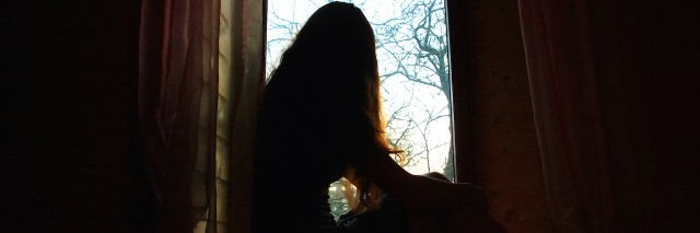 Woman sitting by the window in shadow