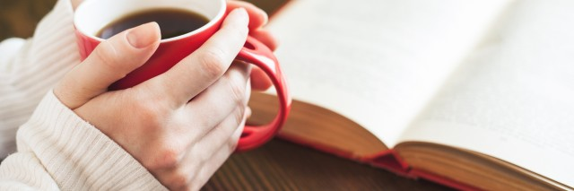 A close-up of hands holding a red mug filled with coffee on a wooden table next to an open book