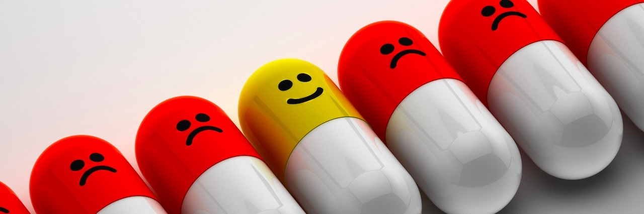 pills lined up with frowney faces on them. One has a happy face.