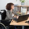 Businesswoman with a disability interviewing candidate at desk in office.