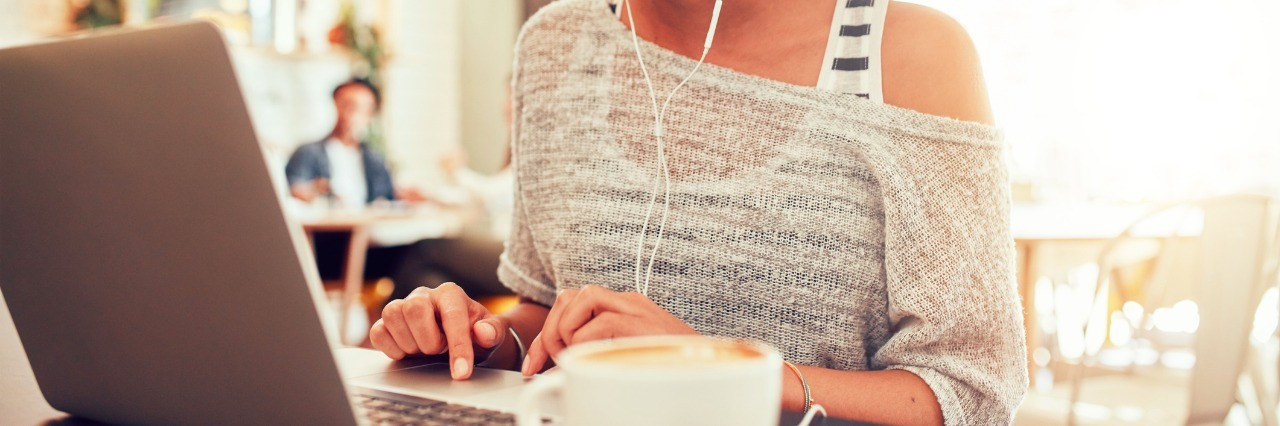Image of happy woman using laptop while sitting at cafe. Young african american woman sitting in a coffee shop and working on laptop.