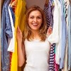 Beautiful girl is smiling and looking at camera while standing among clothes in her dressing room