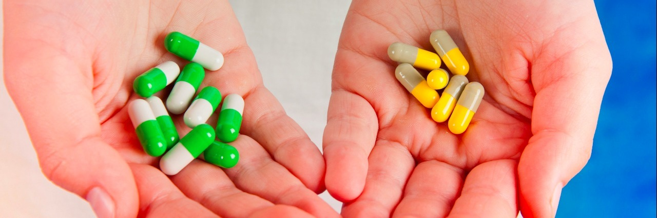Medical pills green, yellow, grey, white in human's hands