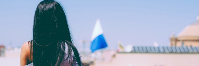 Young girl with a long streight black hair looking at the view from the balcony