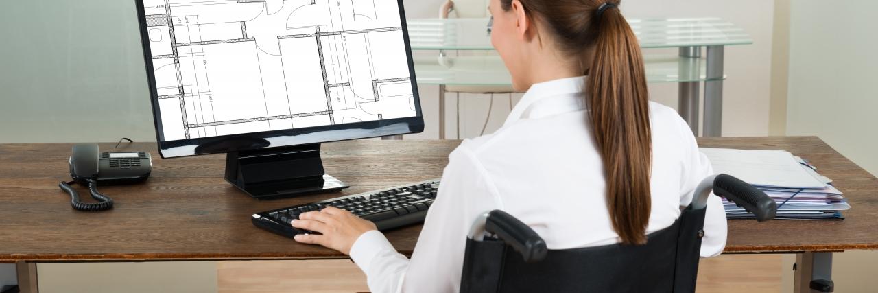 Woman in a wheelchair using a computer.