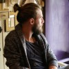 A man with a beard sitting in a cafe, looking outside