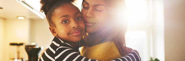 Loving child hugging mother looking at camera looking calm