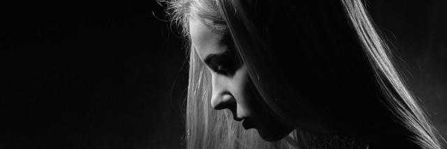 sad pensive girl profile on black background, monochrome image