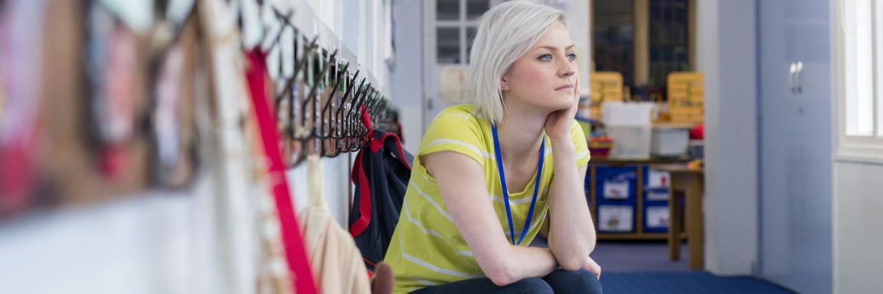 Young, female teacher sitting on a bench in the cloakroom of school. She is looking pensively out of the window.