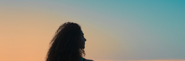 Silhouette of woman in front of the sky at sunset