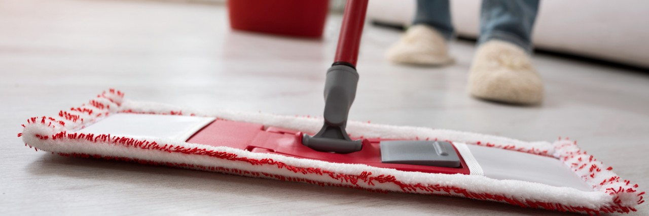 Closeup of human cleaning mopping floor