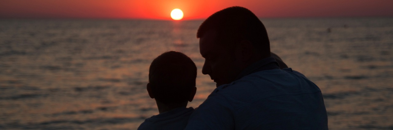 father and son at sunset on the sea