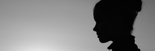 Silhouette of the girl in the nature at summer sunset in black and white.