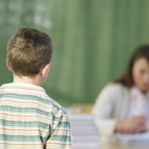 Student approaching teacher at her desk, working on papers