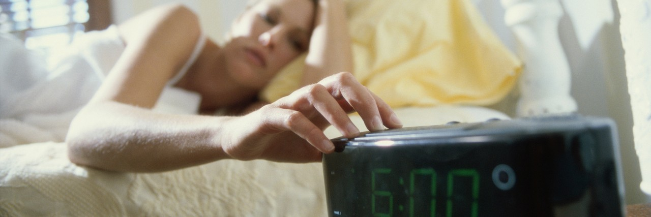 Woman lying in bed reaching for an alarm clock