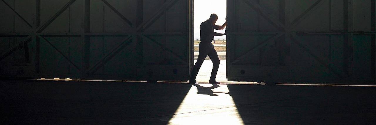 man pushing door open
