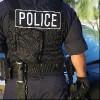 Police officer in bulletproof vest, back view.