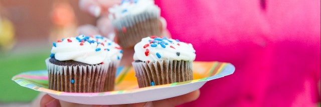 Hand holding plate of cupcakes outdoors