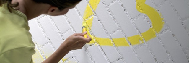 Rear view of a woman painting a yellow heart on a brick wall