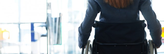 rear view of a businesswoman sitting in a wheelchair in an office