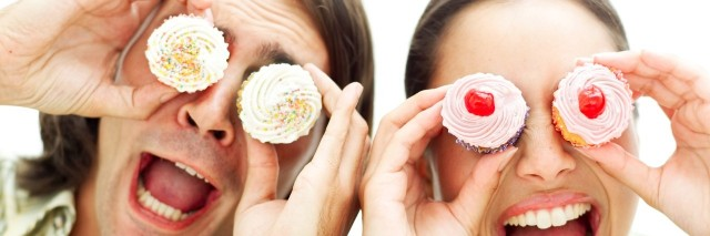 portrait of a young couple holding cupcakes up to their eyes