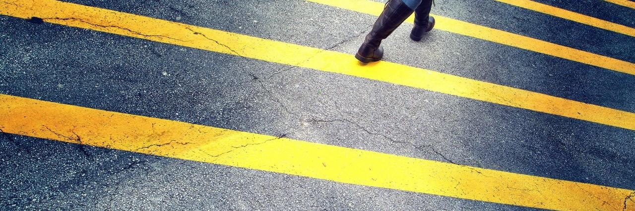woman walk on asphalt floor with yellow lines