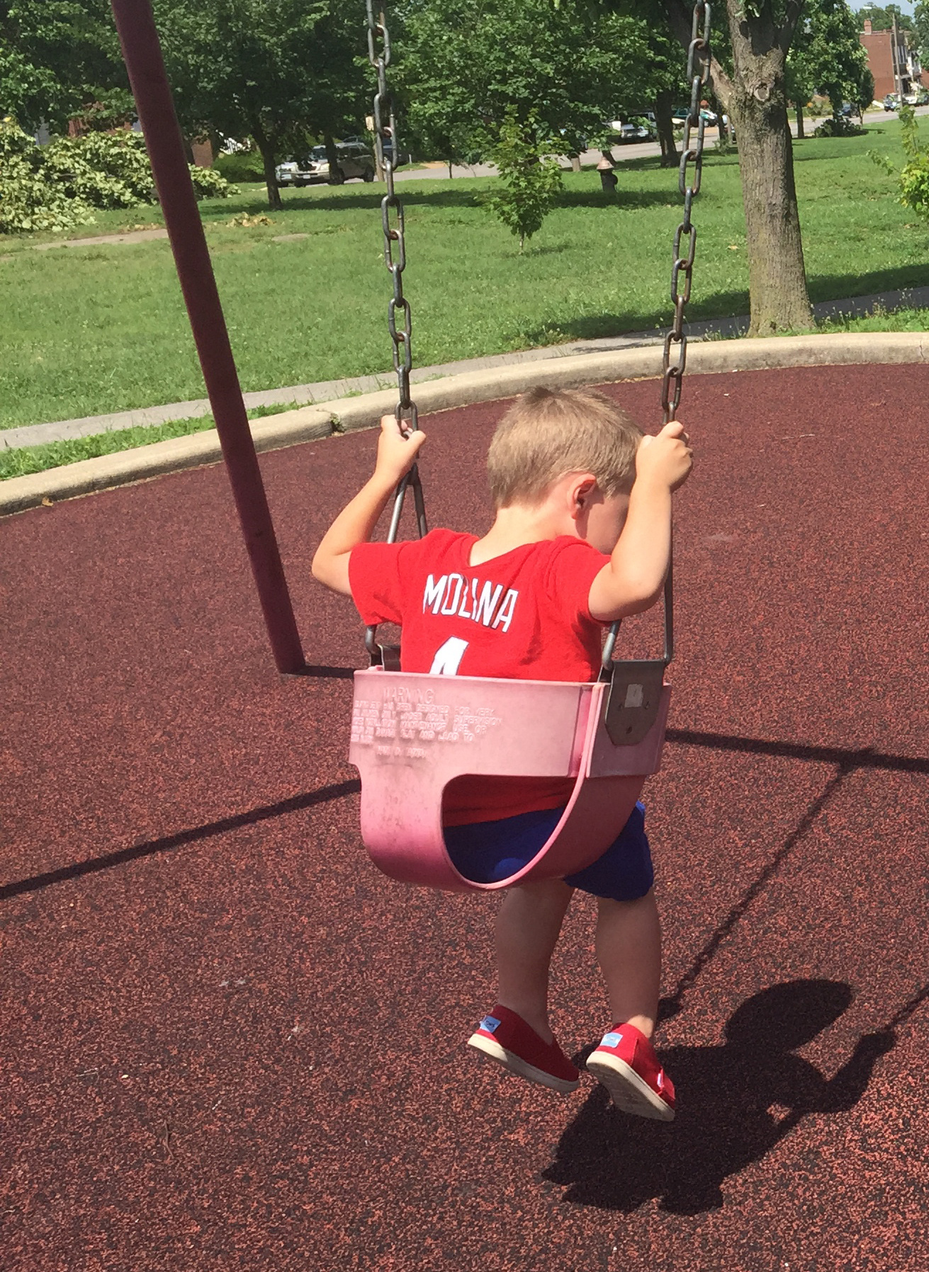 The author's son wearing a Yadier Molina shirt on the swing