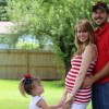 man, pregnant wife and their young daughter in backyard