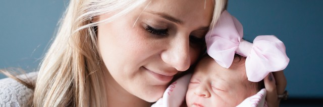 professional photo of woman with newborn baby wearing pink bow