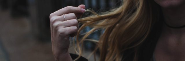 blonde woman playing with hair in anxious manner