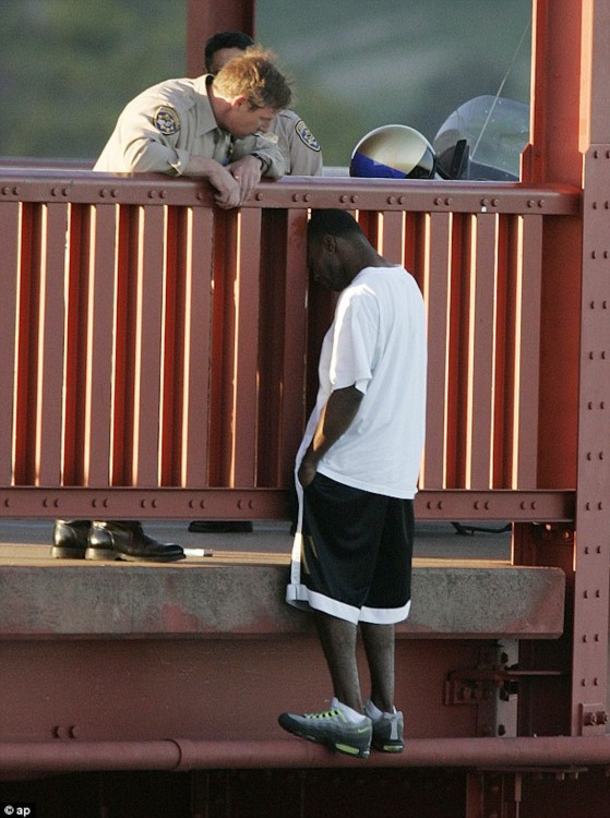 Highway Patrol Sergeant Kevin Briggs listens to Grateful Berthia as he stands on the edge of the Golden Gate Bridge
