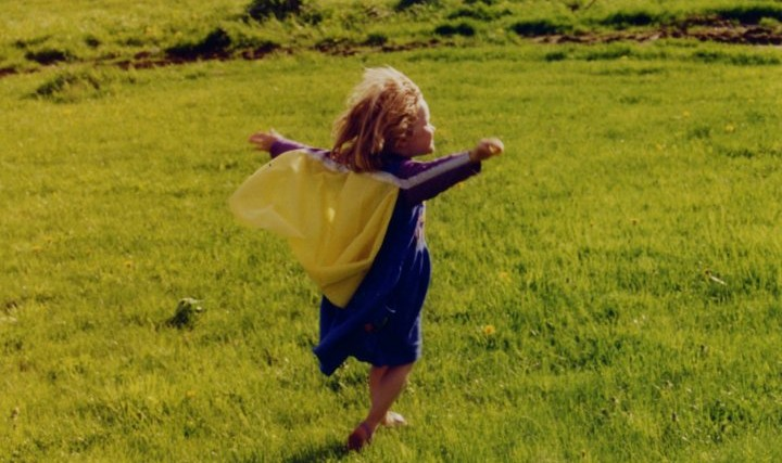little girl running with arms up across grass field