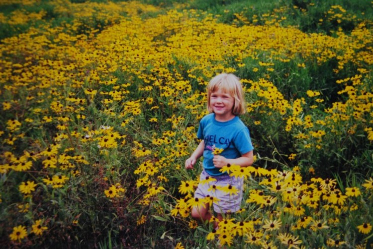 young girl in field of yellow flowers