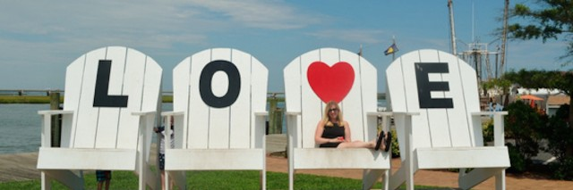 Woman sitting on large white chairs that spell out LOVE