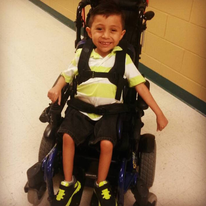 Chris' son with SMA smiling in his wheelchair