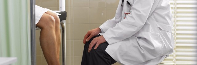 doctor facing patient sitting on table