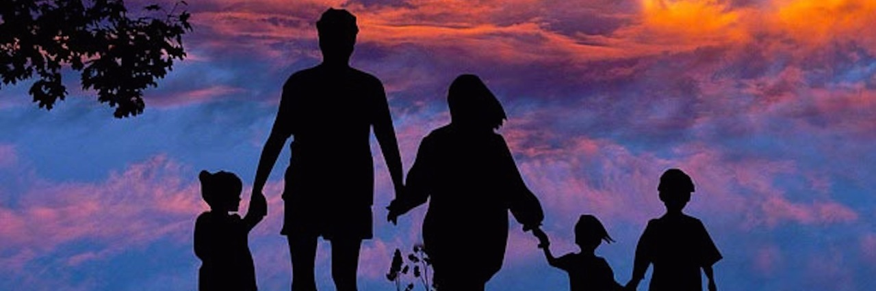 Silhouette of family against sunset sky