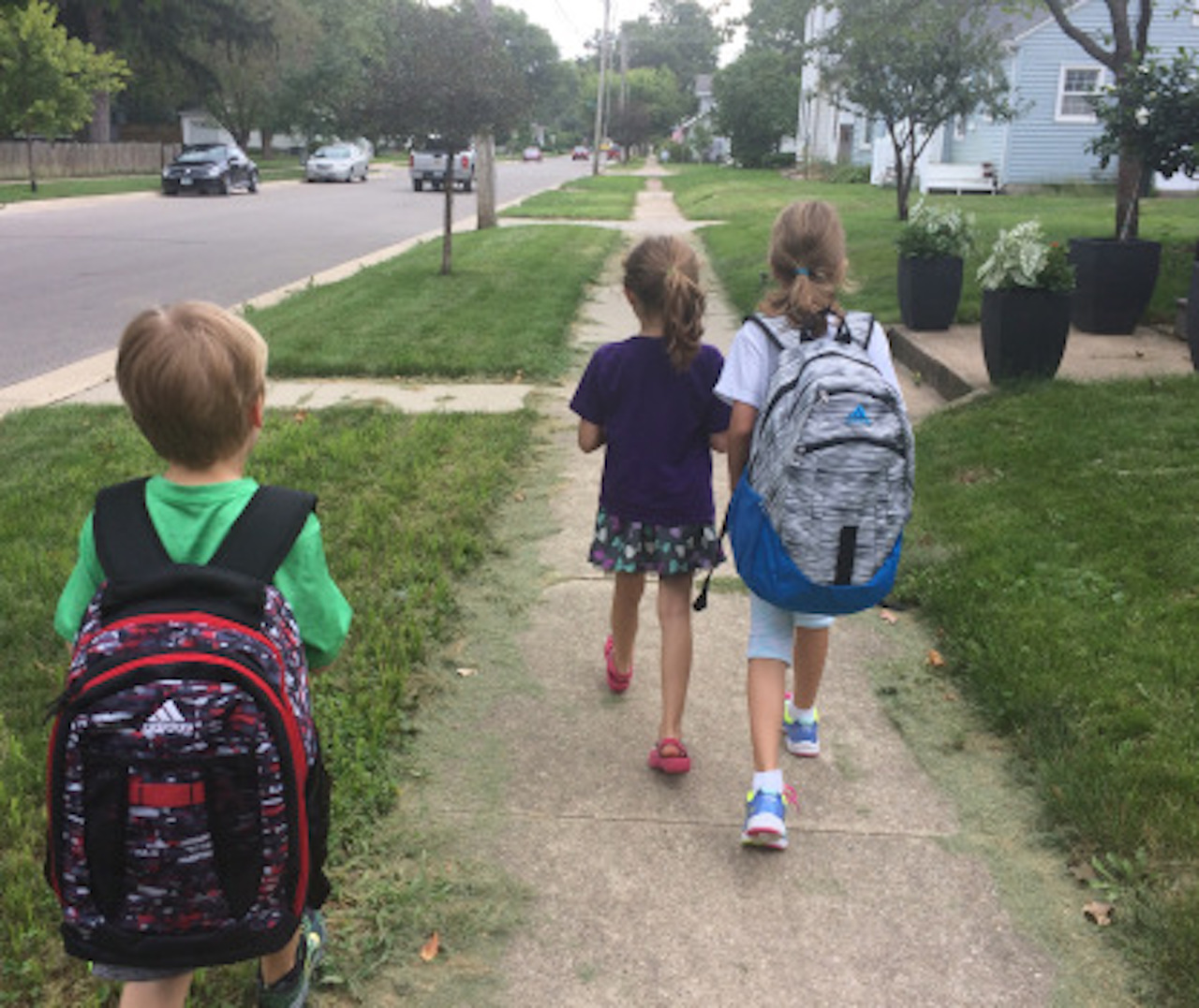 three kids walking to school
