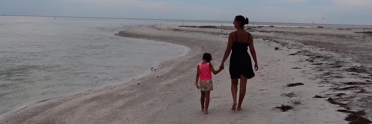 The author and her daughter walking on the beach