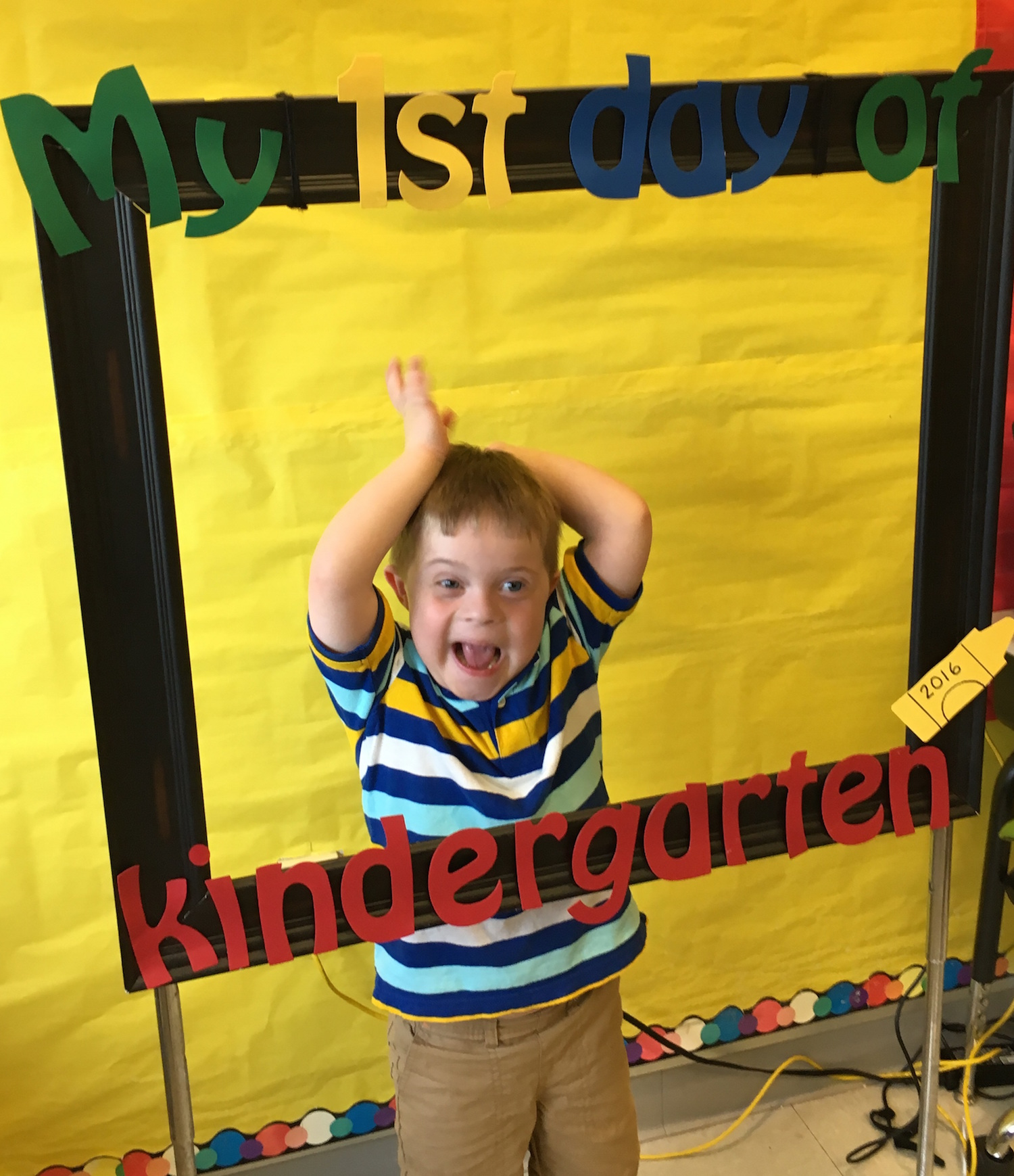 "The author's son standing behind a frame that says ""My 1st Day of Kindergarten"""