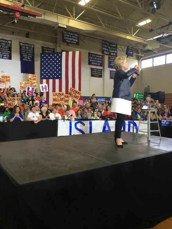 At this Hillary Clinton rally, the interpreter was forced to stand behind the barrier, making her difficult to see and creating a potentially unsafe situation for her. (Interpreter is on the left, wearing a blue dress.)