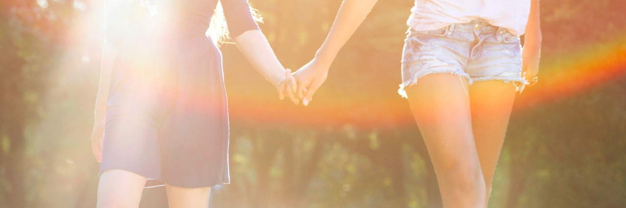 two women holding hands and walking in park