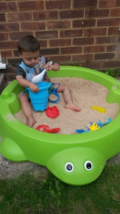 young boy with down syndrome plays in a sandbox