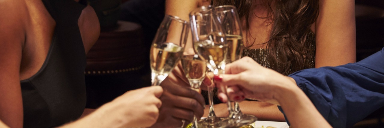 Group Of Female Friends Enjoying Meal In Restaurant and toasting glasses