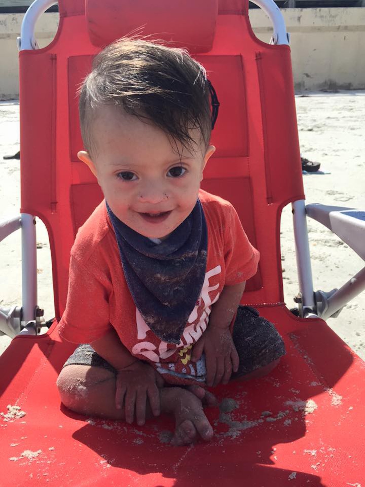 little boy with down syndrome sitting in a chair on the beach