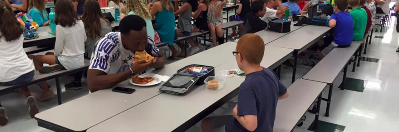 boy and football play sit at lunch table