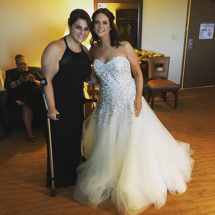 bride in wedding dress next to woman standing with crutch
